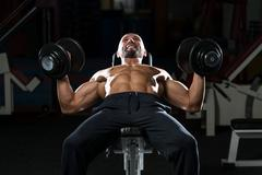 mature man doing dumbbell incline bench press workout - stock photo