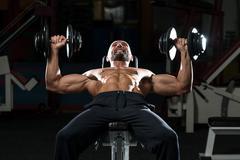 Mature man doing dumbbell incline bench press workout Stock Photos