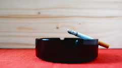 Cigarette burning in black ashtray on the table. Stock Footage