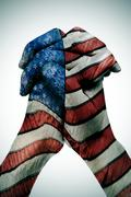 man clasped hands patterned with the american flag - stock photo