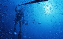 Scuba diver on ascent line - stock photo