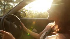 Woman driving car in afternoon sun Stock Footage