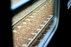 rails shot through the window from inside of a fast, driving train. - stock photo