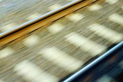 blurred rails shot from a fast, driving train. - stock photo