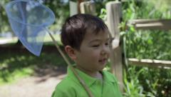Asian Boy Walks On A Path Through A Park With A Butterfly Net Over His Shoulder Stock Footage