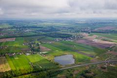 Aerial vista over farm and village - stock photo