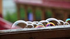 Soap bubbles on wet wooden veranda railing. Stock Footage