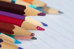 multi-colored pencils on the writing-book page close up - stock photo