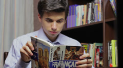 Male student learning French in library, having difficulties Stock Footage