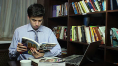 Man studying in library, reading French book, learning process Stock Footage