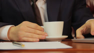 Stock Video Footage of Office worker drinking coffee, checking information on laptop