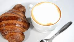 Croissant and cappuccino on a white plate rotating. Stock Footage