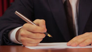 Stock Video Footage of Male boss putting his signature on papers, signing an agreement