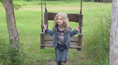 Cutie little girl on a swing in the park - stock footage