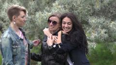 Three beautiful women girlfriends posing on camera Stock Footage