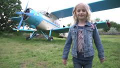 Cutie little girl on the background of the airplane - stock footage