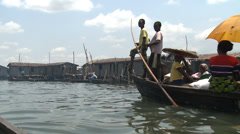 Canoe full of brightly dressed women, Makoko floating slum Stock Footage