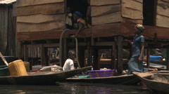 Selling drinking water from canoe, Makoko floating slum Stock Footage