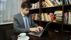 Freelancer works on computer, typing message, studying library, click for HD Stock Footage