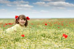 Stock Photo of happy little girl on wildflowers meadow spring season
