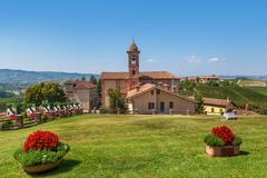 Green lawn and red church in piedmont, italy. Stock Photos