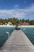 Idyllic beach on an atoll in the Maldives with bungalows on wooden jetty Stock Photos