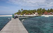 Stock Photo of idyllic beach on an atoll in the Maldives with bungalows on wooden jetty