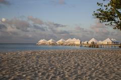 beach on an atoll in the Maldives with bungalows on wooden jetty - stock photo