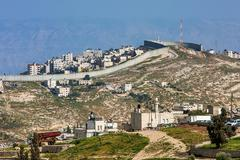 palestinian town behind separation wall in israel. - stock photo