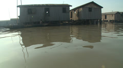 Canoe into shot, big jib move up and out to GV Makoko floating slum Stock Footage
