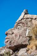 Inca face sculpture in the peruvian andes at puno peru Stock Photos