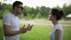 Young couple having fight in summer park Stock Footage