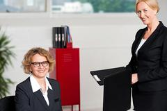 Stock Photo of Woman handing over files to her female boss
