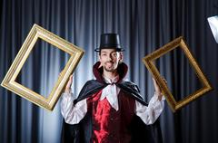 Magician with photoframe in studio - stock photo