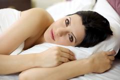 Serene woman relaxing in bed Stock Photos