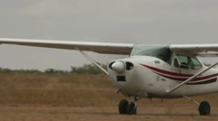White aircraft Cessna 182L Skylane rides on the field Stock Footage