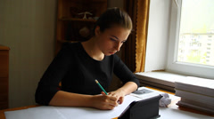 Young girl student working on the tablet and writes on paper Stock Footage