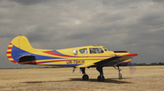 Medium shot Yellow plane Yakovlev Yak-18T awaits clearance to take off. Passing - stock footage