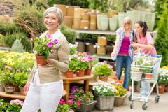Garden center senior lady hold potted flower - stock photo
