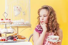 Fancy sweet tooth drinking tea in studio - stock photo