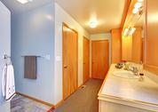 Bathroom house interior with many doors to closets. Stock Photos