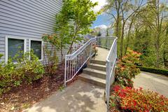 Large grey house exterior of modern home with walkway. Stock Photos