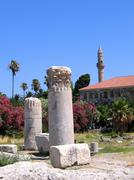 Antique greek columns and minaret of the mosque Stock Photos