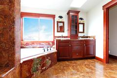 Luxury new home bathroom with red marble and mahogany wood. Stock Photos