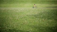 Little girl cycling in park on a pink bike. Slow motion Stock Footage