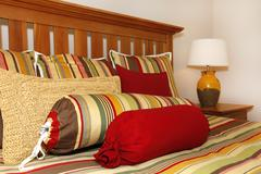 bed details in red, yellow and green with wood head board. - stock photo