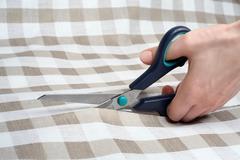 Cutting fabric closeup. Dressmaker at work. Fabric cutting scissors. Tailoring Stock Photos