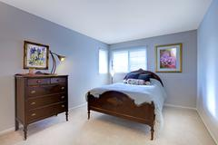 Blue bedroom with dark wood bed and dresser. Stock Photos