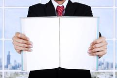 Businessman holding blank open book at office Stock Photos