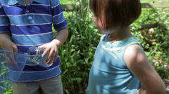 Children Stop On A Trail, To Put Bug In A Jar, Then Continue Walking - stock footage